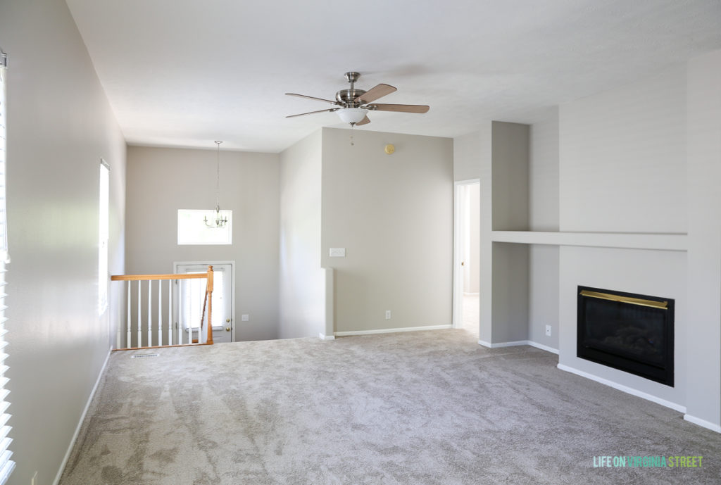The upstairs room with a refreshed carpet and fireplace.   There is a ceiling fan.