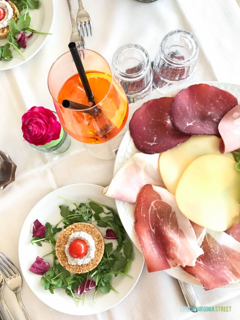 A table set with aperol spritz, salad, and meat and cheese tray.