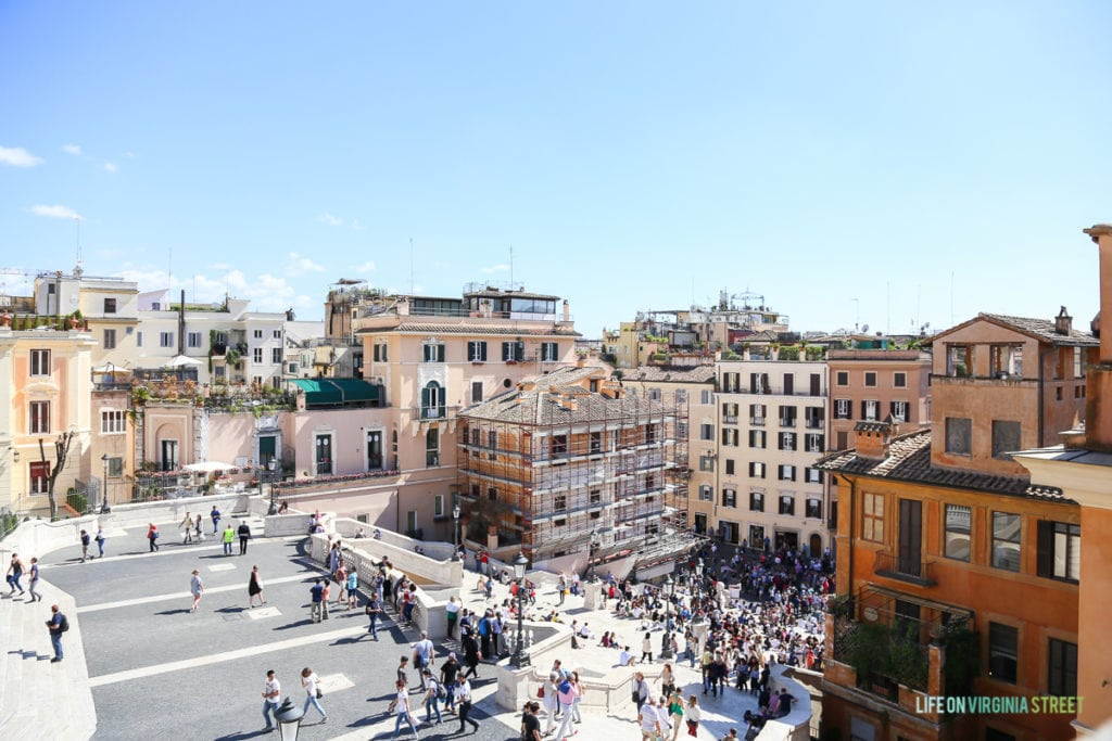 People gathered in a square in Rome on a sunny day.