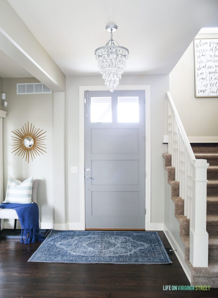 Entryway and front door. Front door color is Behr Elephant Skin and the walls are Behr Castle Path. Love the blue vintage style rug and gold sunburst mirror.