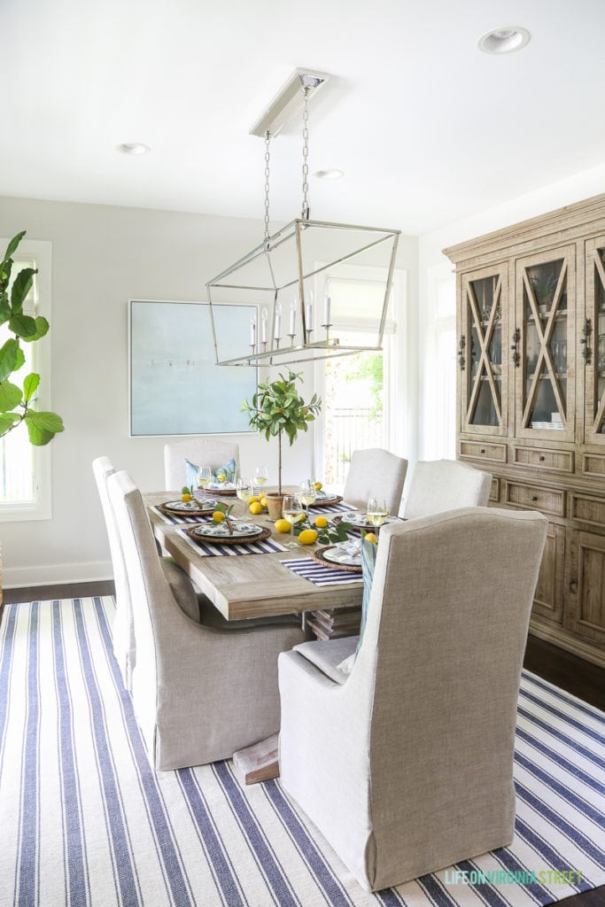 A beautiful summer tablescape inspired by the Amalfi Coast in Italy. Lemons, navy blue and white stripes, linen chairs, Darlana linear pendant, wood hutch, beach art, Dash & Albert striped rug, reclaimed wood table and wine!