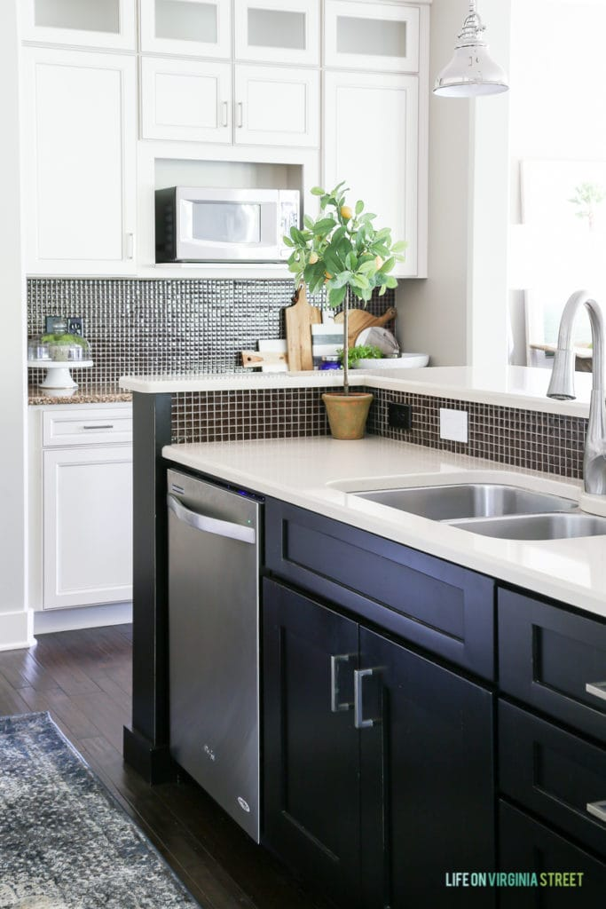 A white kitchen with black island, quartz countertops, chrome pendants, and a blue and brown vintage-inspired rug.