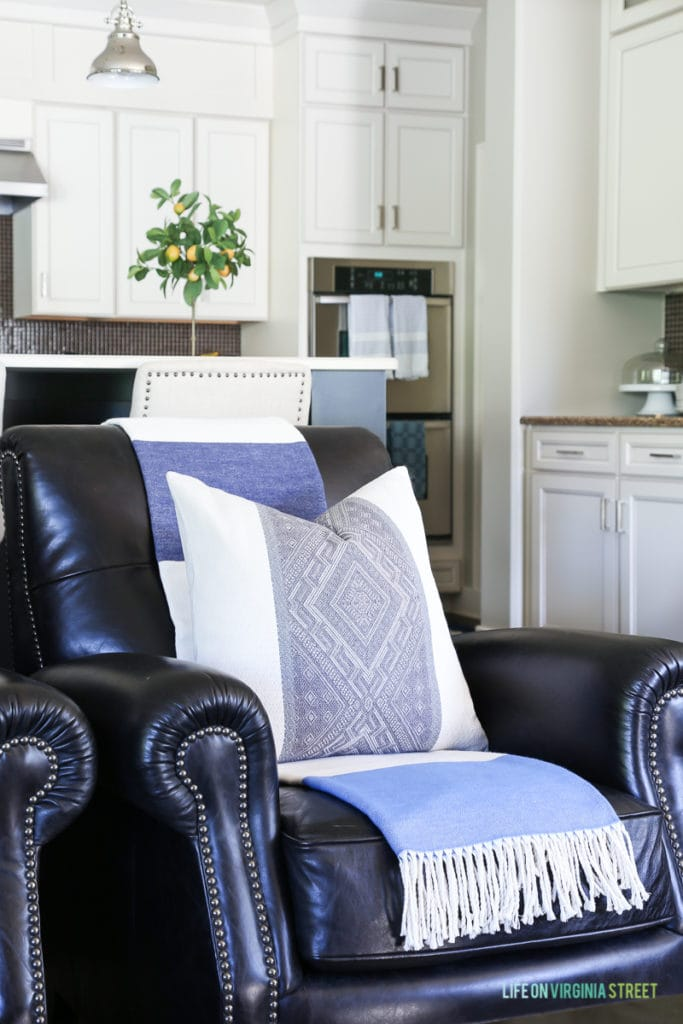 Love this idea: lighten dark leather furniture (chairs or couches) by adding a light, colorful throw over the back. This blue and white striped throw adds a coastal vibe and helps lighten the dark leather chair.