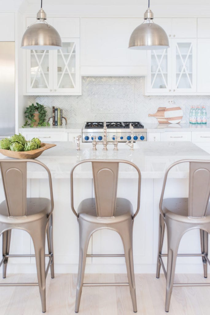 White kitchen with marble herringbone backsplash, silver metal barstools, artichokes in a wood bowl, and blue knobs on the gas stove.