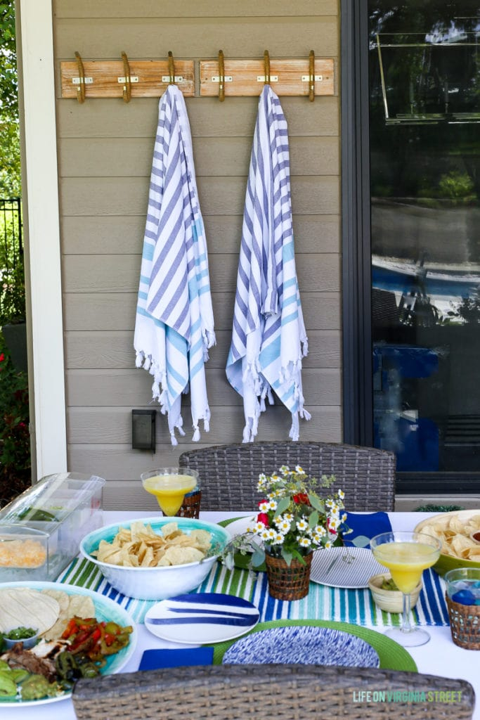 Blue and white blankets hanging outside on hooks by the table.