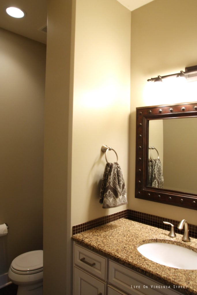 An off white bathroom with a brown mirror and speckled brown countertop.