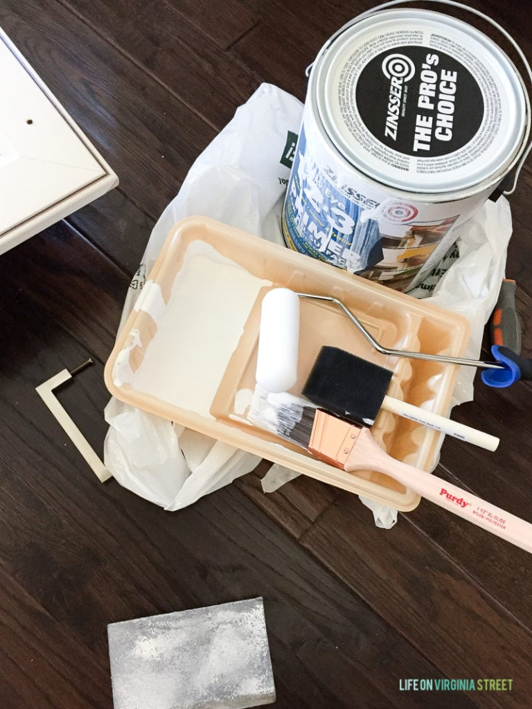 Supplies need to paint thermofoil cabinets. A sanding block, paint tray, paint brush, foam roller, foam brush and Zinsser 1-2-3 primer.