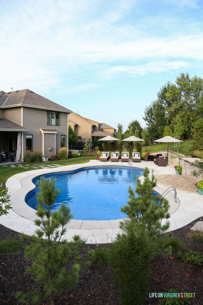 Gorgeous oasis shaped vinyl pool. Striped umbrellas, striped outdoor curtains, lounge chairs, waterfall, stone veneer, oleander and pine trees.