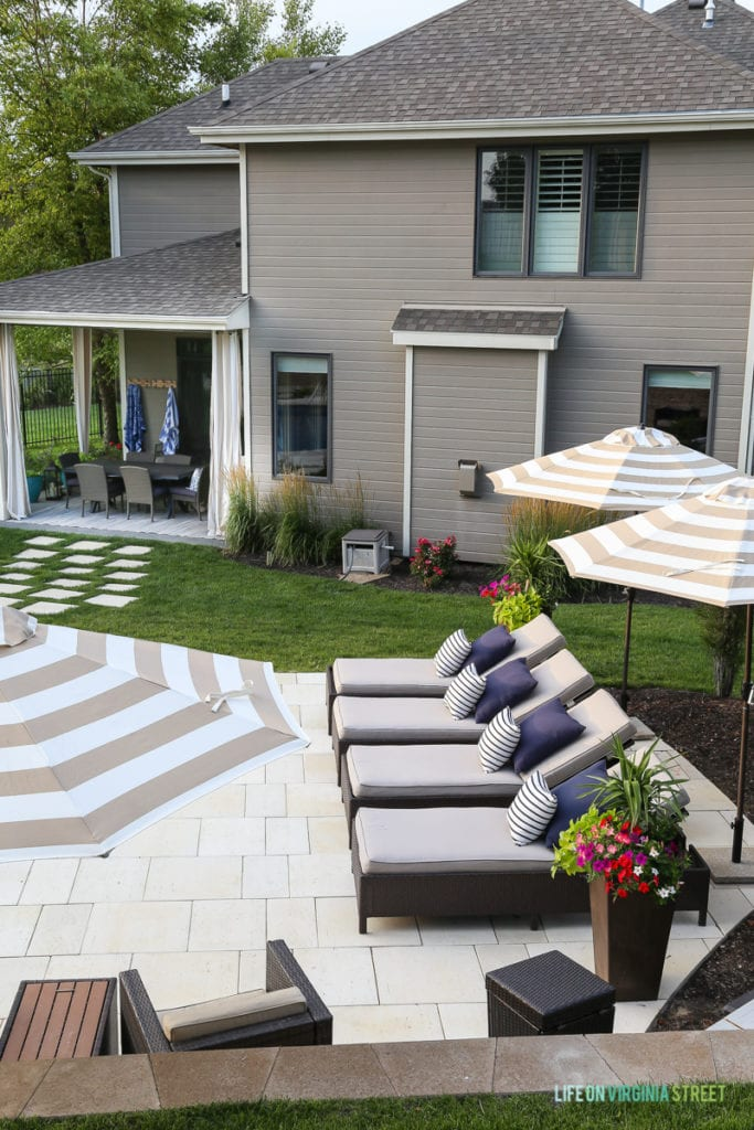 Gorgeous oasis shaped vinyl pool. Striped umbrellas, striped outdoor curtains, checkerboard pathway, concrete travertine pavers, lounge chairs, navy blue pillows, striped pillows and planters filled with annuals.