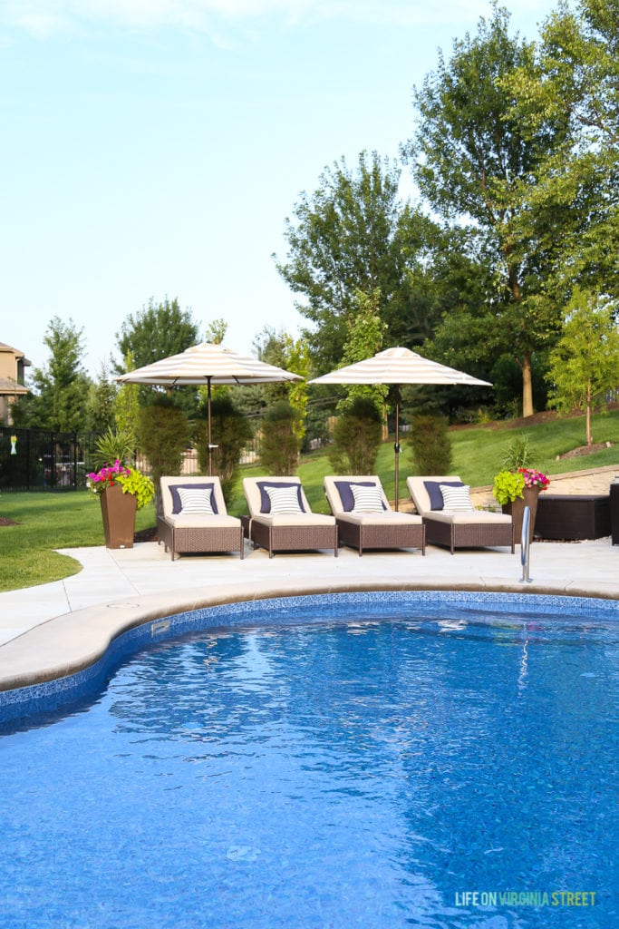 Backyard Pool Review after one year of ownership. Gorgeous oasis shaped vinyl pool. Striped umbrellas, striped outdoor curtains, lounge chairs, navy blue pillows, striped pillows and planters filled with annuals.