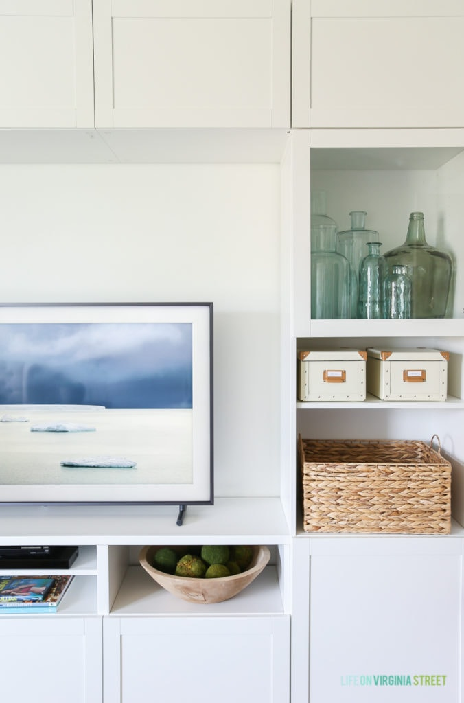 Completely blown away by this TV that looks like art (The Frame from Samsung). Also loving this craft room / TV room painted in Benjamin Moore Simply White. The IKEA BESTA stores fabric and other crafts, and the navy blue rug, fig tree and sisal poufs add color and texture. The blue and green recycled glass bottles are so pretty here! #ad