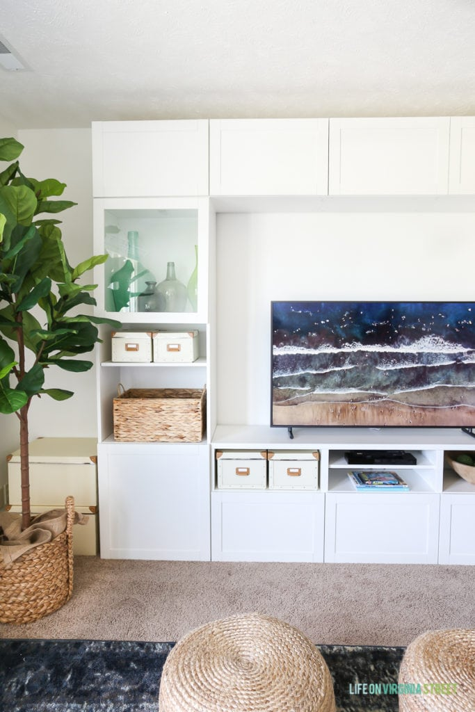 Completely blown away by this TV that looks like art (The Frame from Samsung). The beach scene on the television is perfect for this space. Also loving this craft room / TV room painted in Benjamin Moore Simply White. The IKEA BESTA stores fabric and other crafts, and the navy blue rug, fig tree and sisal poufs add color and texture. The white scalloped flushmount light fixture is perfection! #ad