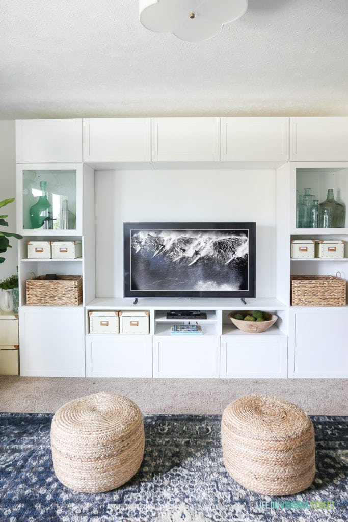 Check out this TV that looks like art (The Frame from Samsung). TV room painted in Benjamin Moore Simply White. The IKEA BESTA stores fabric and other crafts, and the navy blue rug, fig tree and sisal poufs add color and texture. The white scalloped flushmount light fixture is perfection! #ad