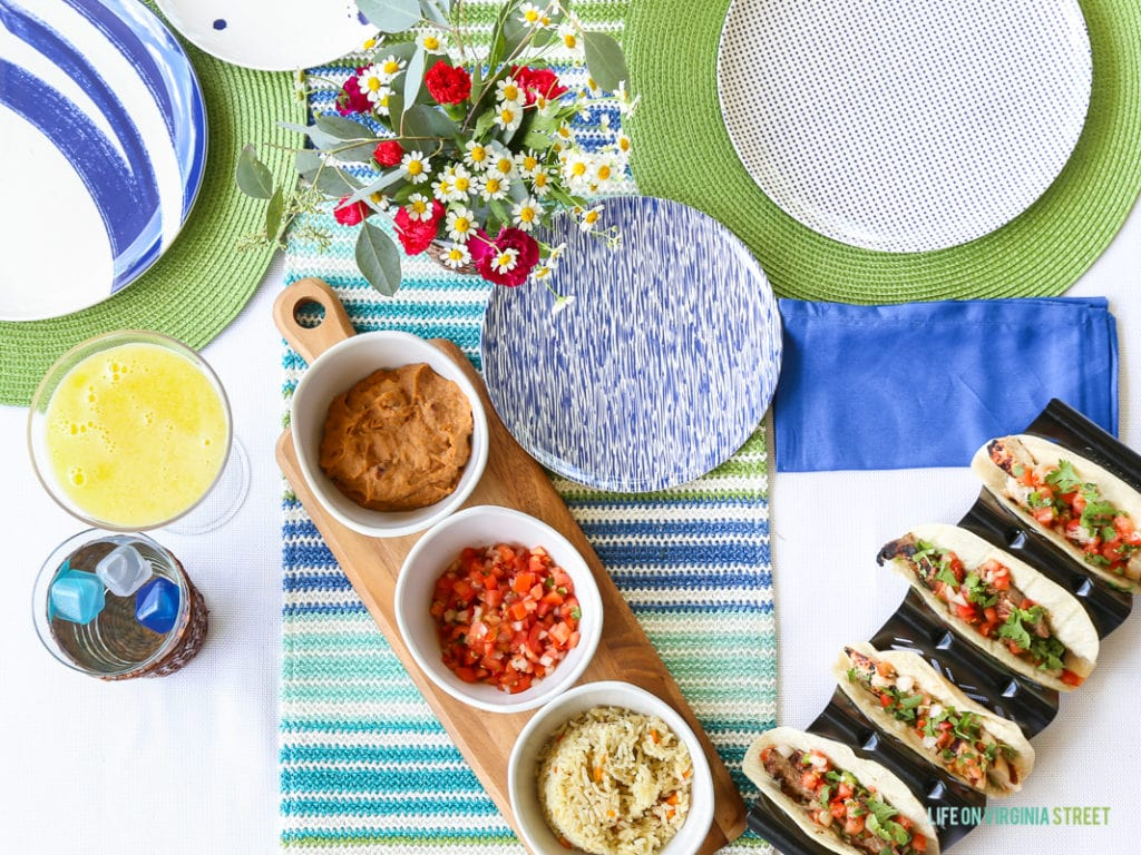 Salsa, guacamole on a wooden board, and tacos half made with flowers on the outdoor table.