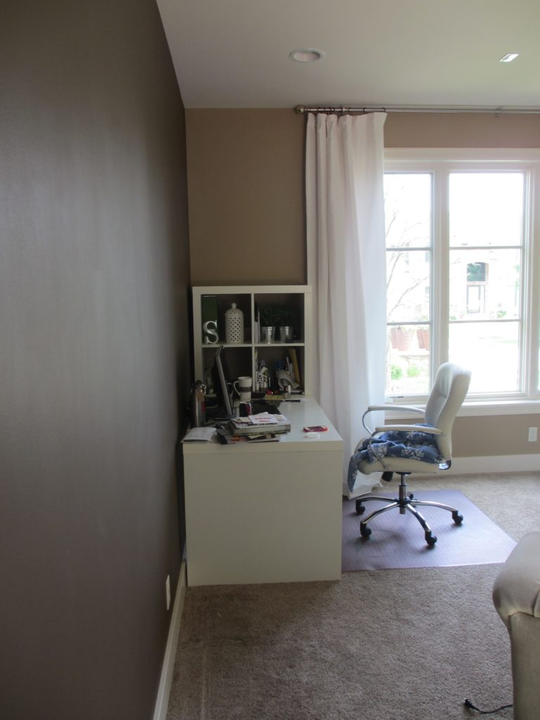 Office with carpet, white desk and white shelving unit.