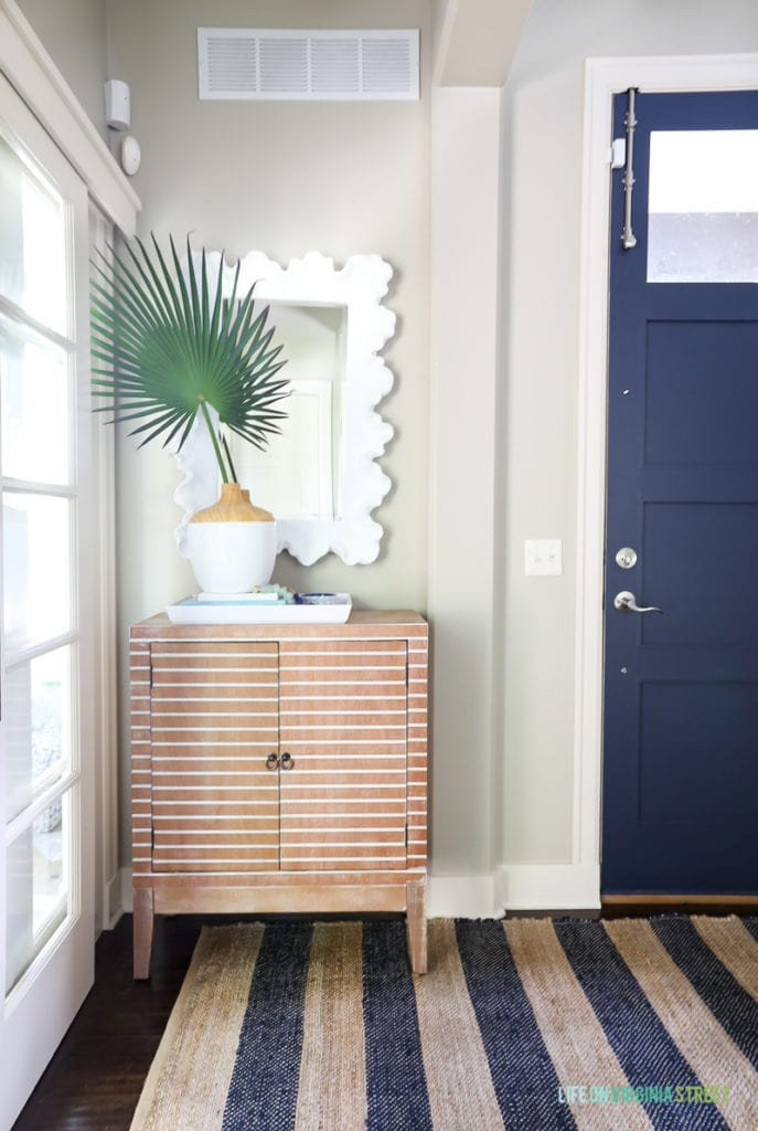 Coastal style entryway update with navy blue jute striped rug, striped wood cabinet, palm fronds, coral style mirror and Benjamin Moore Hale Navy blue painted interior door.