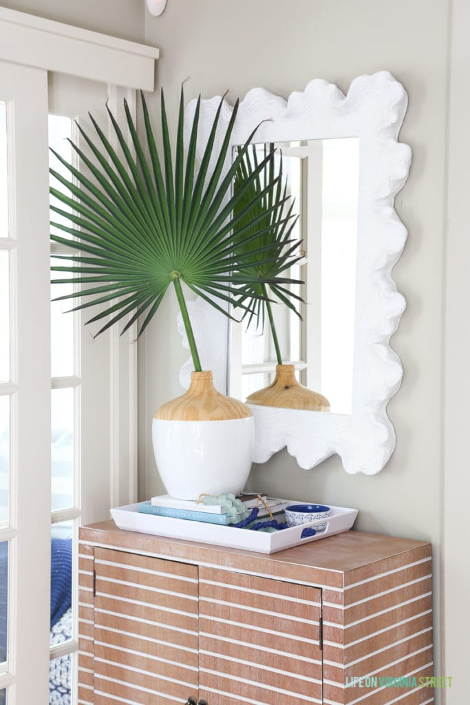 Coastal style entryway update with striped wood cabinet, tray with books and glass beads, palm fronds, coral style mirror.
