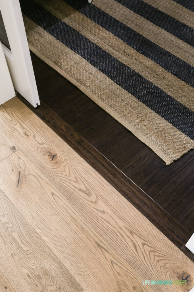 Light oak floors and dark wooden floors with a transition piece in between and striped rug on the floor.