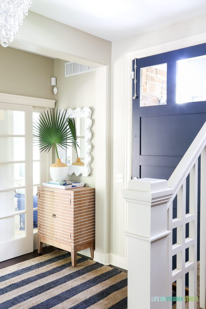 Coastal style entryway update with crystal teardrop chandelier, navy blue jute striped rug, striped wood cabinet, palm fronds, sliding french doors, coral style mirror and Benjamin Moore Hale Navy blue painted door.
