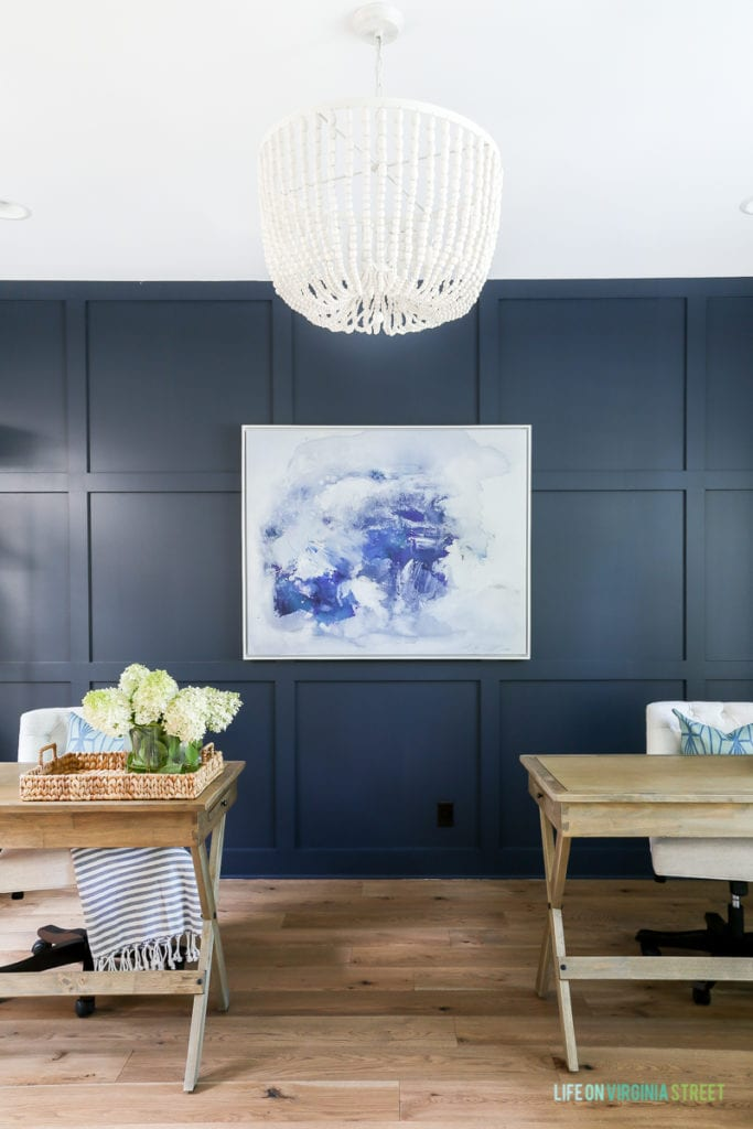 A navy blue wall in office, two desks with a painting behind them and a beaded chandelier.