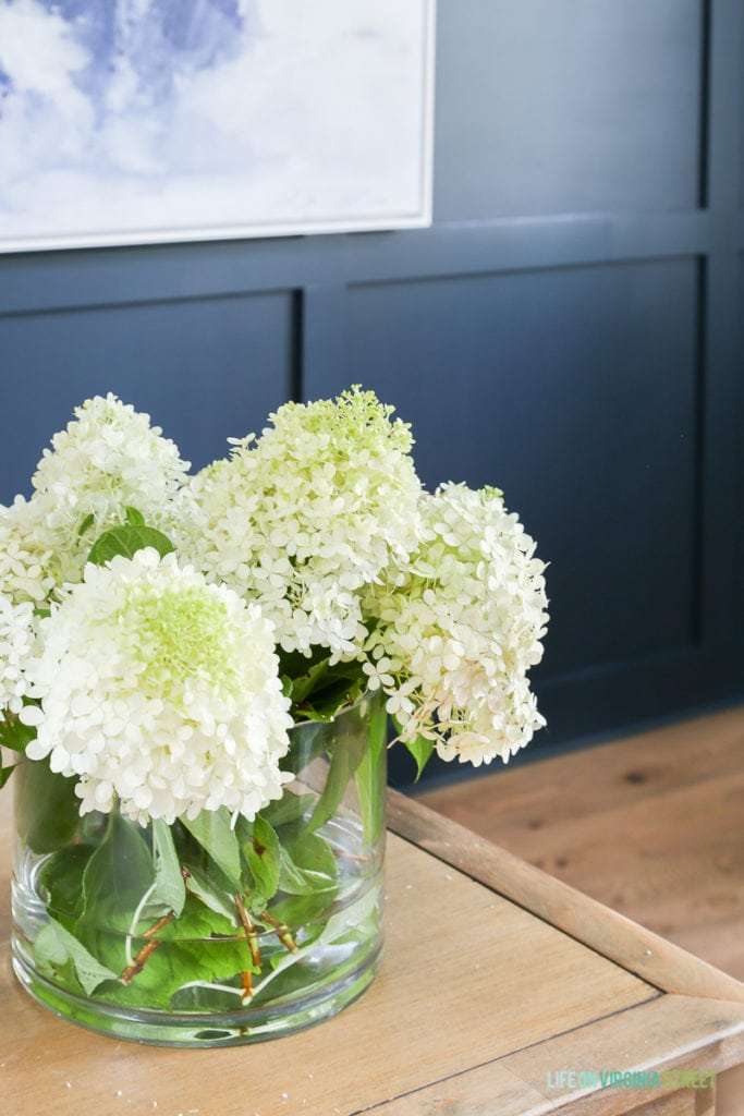 Limelight hydrangeas in a clear glass vase sitting on the desk.