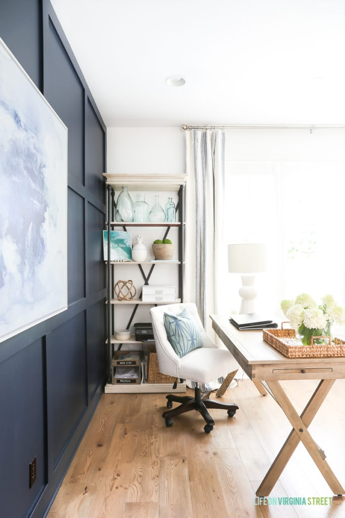 Home office with Benjamin Moore Hale Navy board and batten wall, Simply White walls, navy blue and white abstract artwork, whitewashed bead chandelier, wood desks and Mannington white oak Maison Normandy Bistro hardwood floors. Bookshelf is filled with recycled glass vases, white ceramic pineapple and other coastal decor items.
