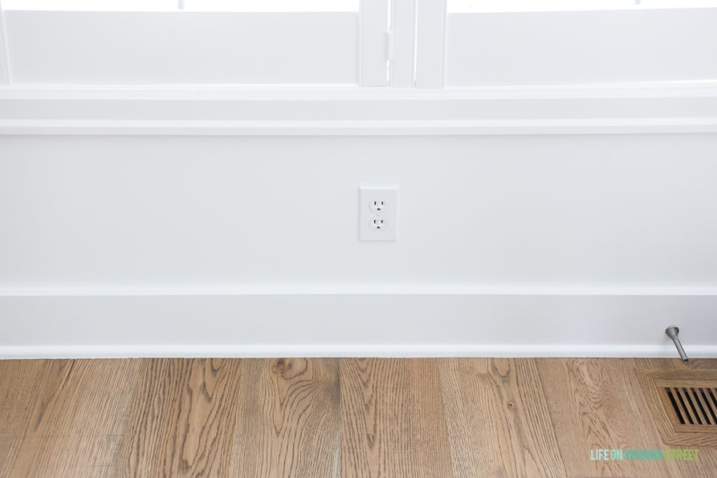 Light colored wooden floors, white walls and white outlet.