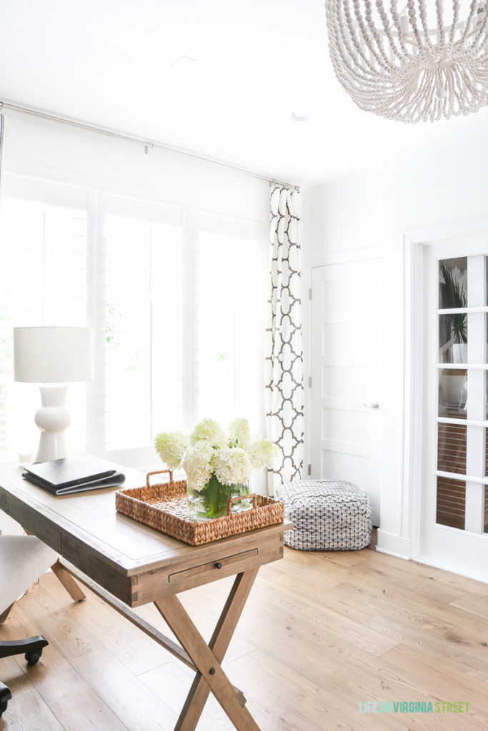 Home office with Simply White walls, whitewashed bead chandelier, Windsor Smith Riad drapes, wood desk, linen office chair, hydrangeas, water hyacinth tray, and Mannington white oak Maison Normandy Bistro hardwood floors.