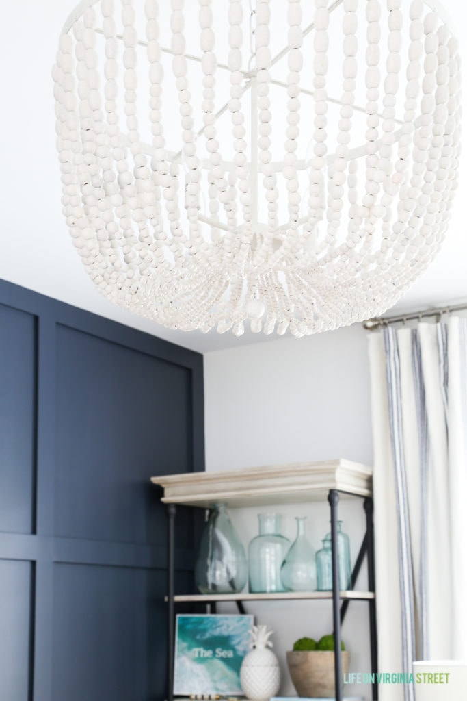 Large white washed beaded chandelier hanging from the ceiling above the desk in the office.