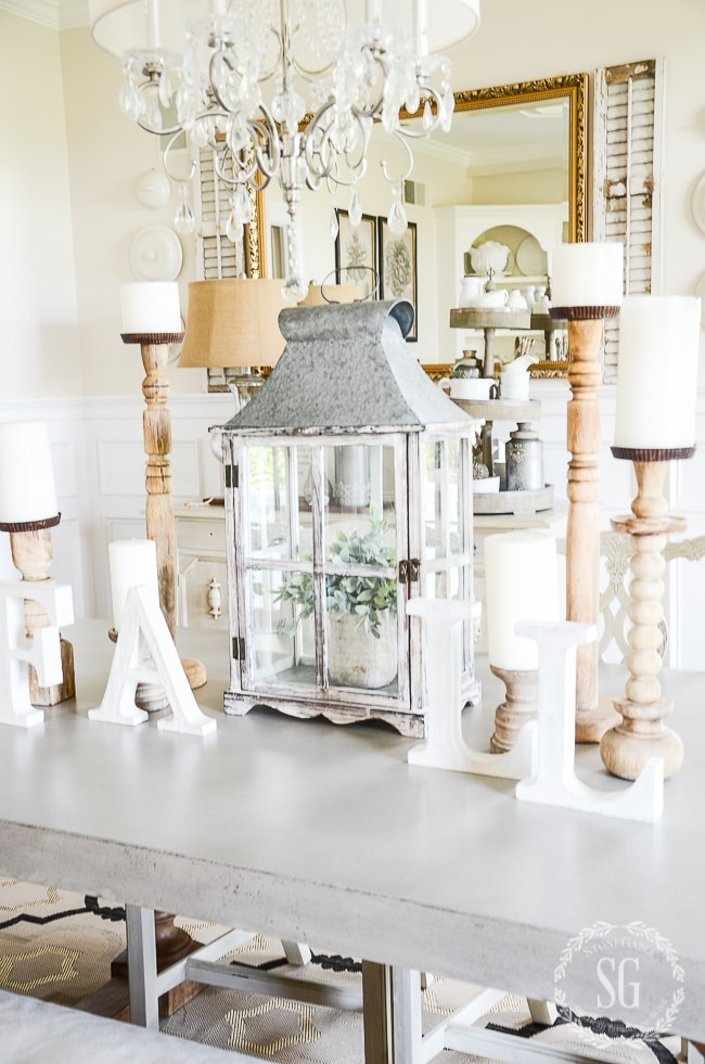 A table with candlesticks and a large mirror behind the table.