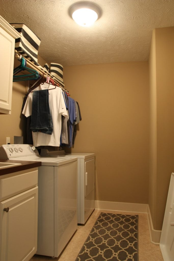 Beige laundry room with clothes hanging above the washer and dryer.