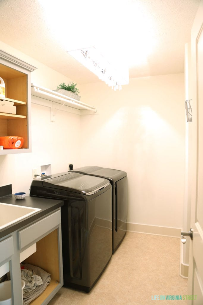 Black washer and dryer and white walls, and grey counter in laundry room.