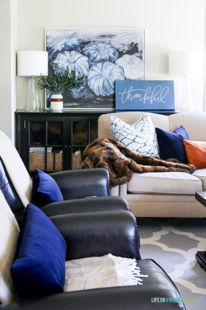 Gorgeous fall living room with navy blue, copper and neutrals. Loving the mix of velvet and faux fur paired with the olive leaves. Also love the large blue pumpkins canvas art and 'thankful' canvas.