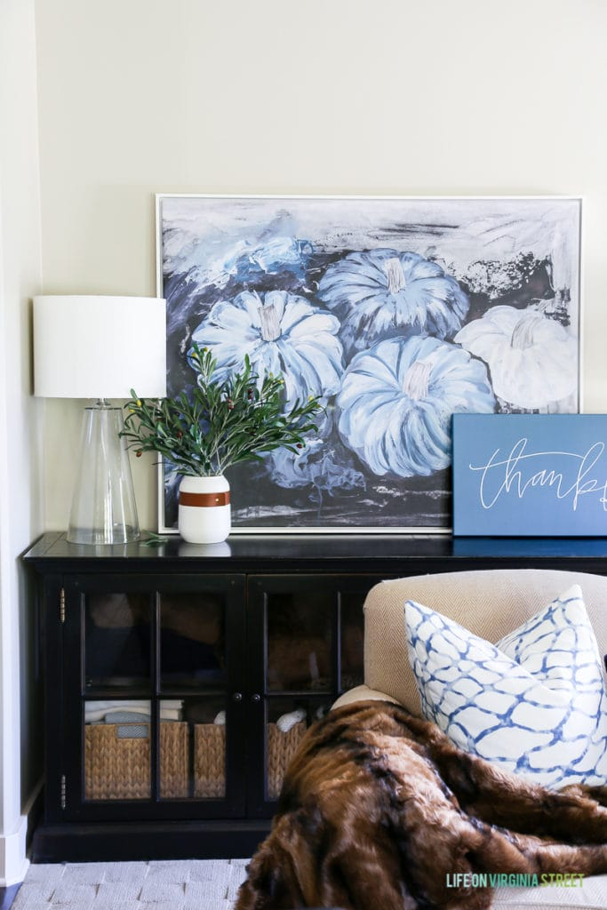 Gorgeous fall living room with navy blue and neutrals with olive leaf accents. Loving the mix of velvet and faux fur. Also love the large blue pumpkins canvas art and 'thankful' canvas.