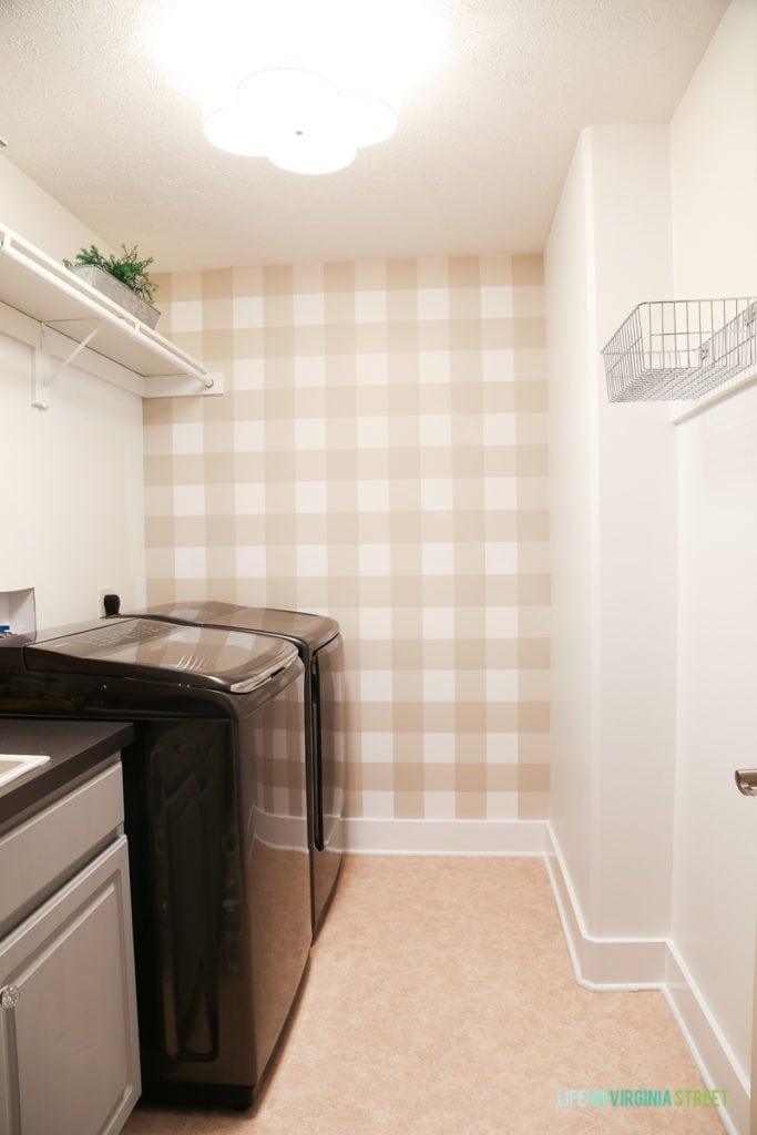 Buffalo checkered wall, painted baseboards and bright lighting fixture in updated laundry room.