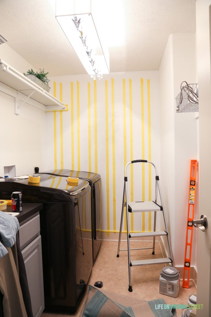 Rows of vertical yellow taped lines on wall in laundry room.