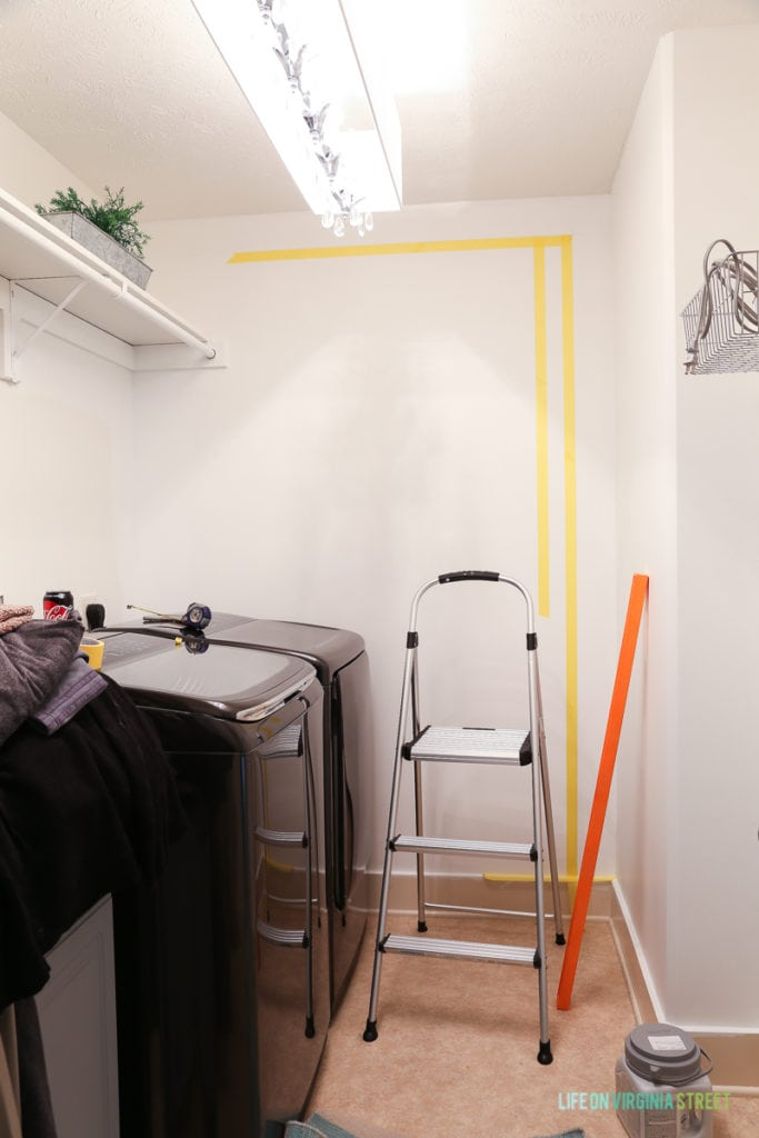 Yellow tape on wall for taping buffalo checks, plus a step ladder in laundry room.