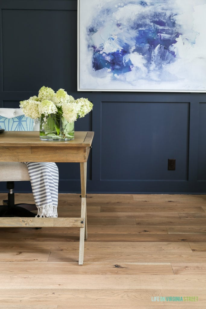 Office with natural wood desk and navy blue board and batten walls.
