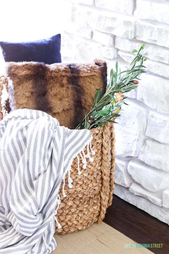 Hyacinth basket with navy blue velvet pillow, faux fur pillow, striped throw and olive leaf branch.