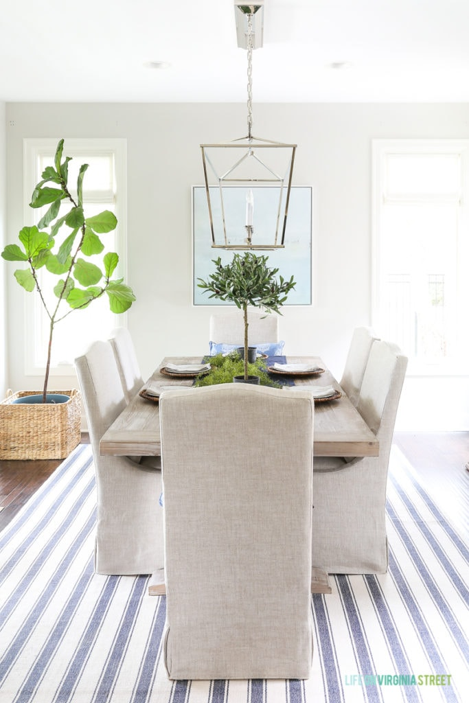 Fall dining room with blue and white striped rug, natural wood table, linen chairs, fiddle leaf fig tree, olive leaf topiaries and beach art. Light fixture is the Visual Comfort Darlana Linear Pendant.