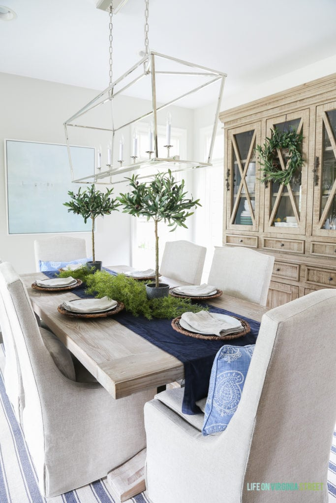 Fall dining room with blue and white striped rug, natural wood table, linen chairs, reclaimed wood hutch with olive wreath, olive leaf topiaries and beach art. Light fixture is the Visual Comfort Darlana Linear Pendant.