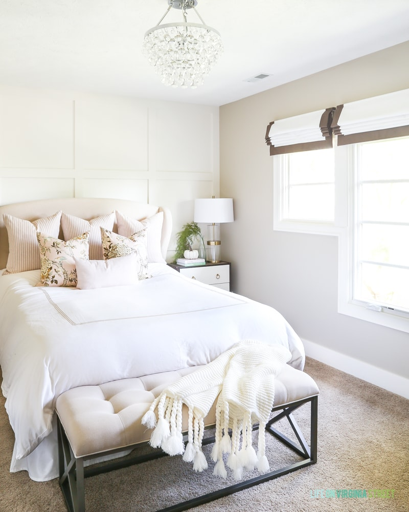 White neutral bed with bench at the foot of bed and a chandelier above.