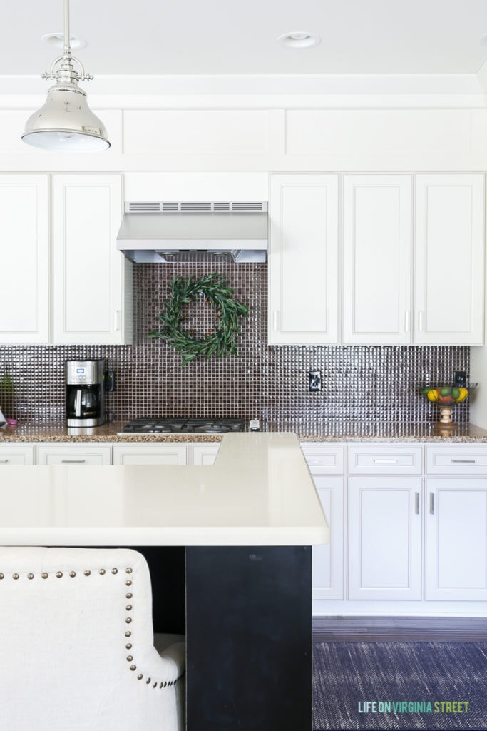 White kitchen with olive wreath over range.