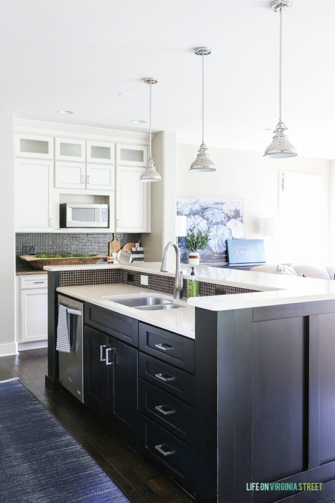 White kitchen with black island, navy blue herringbone rug, and chrome pendants over island.