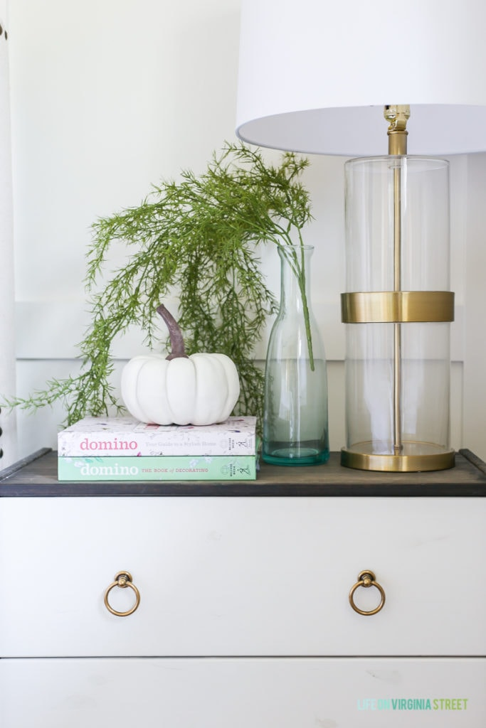 Side table with a white and gold lamp and a pumpkin on books.