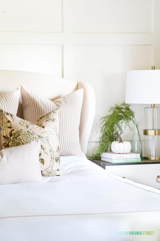 Blush toned pillows on white bedding.