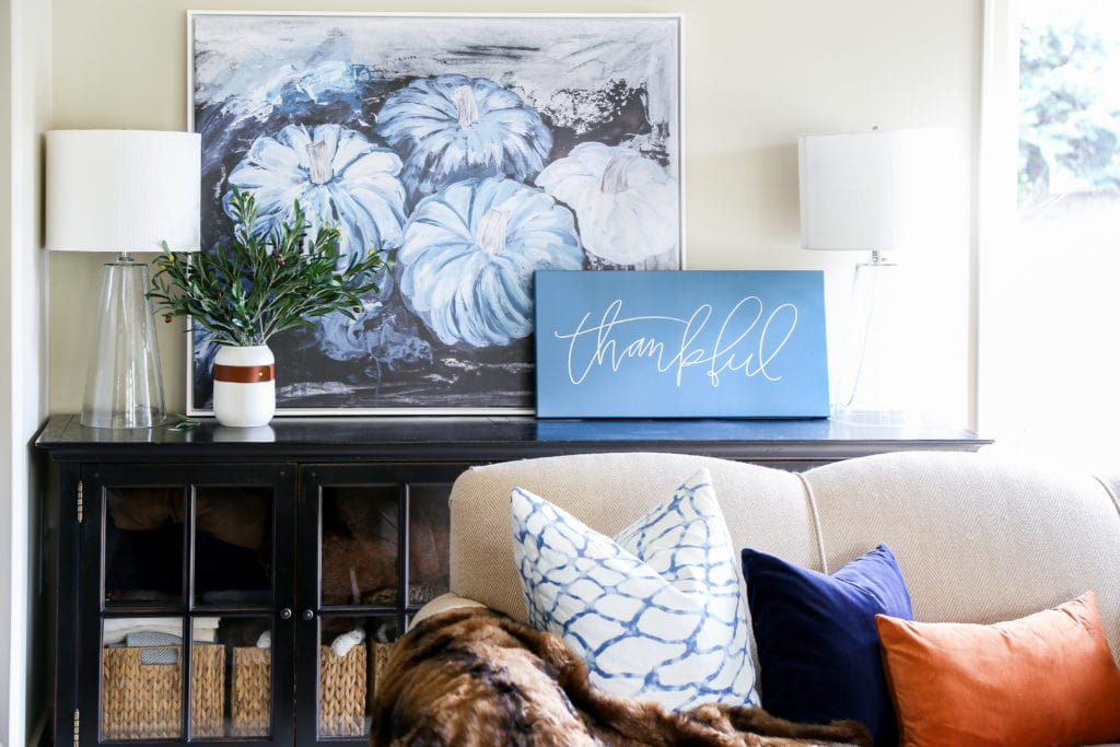Gorgeous fall living room with navy blue, copper and neutrals. Loving the mix of velvet and faux fur. Also love the large blue pumpkins canvas art and 'thankful' canvas.