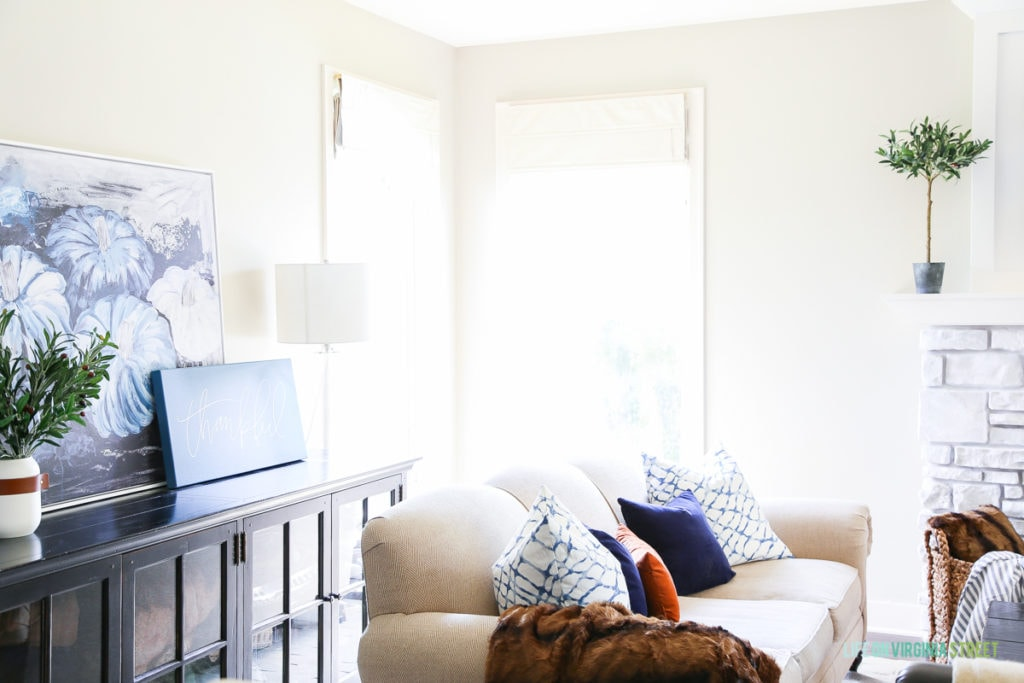 Light and bright fall living room with navy blue, copper and neutrals. Loving the mix of velvet and faux fur. Also love the large blue pumpkins canvas art and 'thankful' canvas.