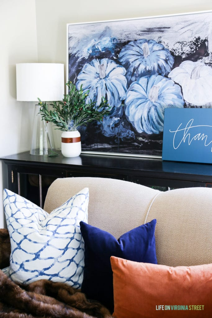 Gorgeous fall living room with navy blue, copper and neutrals. Loving the mix of velvet and faux fur. Also love the olive leaf branches, glass lamps, large blue pumpkins canvas art and 'thankful' canvas.