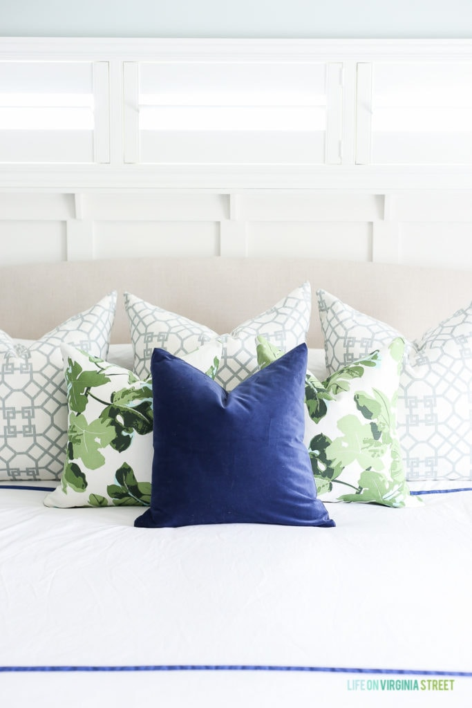 Linen headboard with white bedding, navy blue velvet pillow, fig leaf pillows, trellis pillows, white board and batten and Sherwin Williams Sea Salt walls.